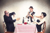 Angry couple disturbed by a trumpet musician while having dinner — Stock Photo