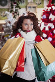 Woman with curly red hair and christmas bag — Stock Photo