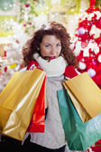 Woman with curly red hair and christmas bag — Stok fotoğraf