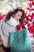 Happy beautiful girl with curly red hair in the Christmas shop — Stock Photo
