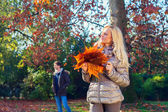 Woman is holding the leaves in autumn — Stock Photo
