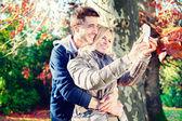 Couple taking selfie in autumn — Stock Photo