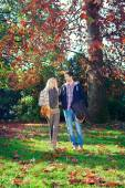 Man and woman walking hand in hand in autumn park — Stock Photo