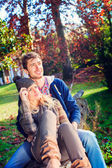 Couple sitting on a tree trunk in a park — Stock Photo