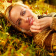 Beautiful woman lying down on autumn leaves — Stock Photo #60530463