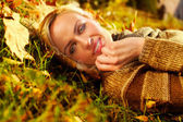 Beautiful woman lying down on autumn leaves — Stockfoto