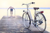 Man parks bike on boardwalk befor jumping into the water — Stock Photo