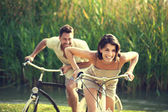 Couple having a bicycles race into the nature — Stock Photo