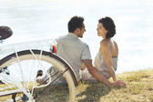 Couple with bicycle resting in front of the lake — Stock Photo