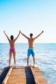 Couple Holding Hands Up at Wooden Pier — Stock Photo