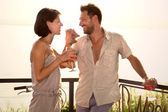 Couple in love jokes at spritztime on the lakeside — Stock Photo