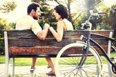 Couple in love sitting together on a bench with bikes — Foto de Stock