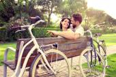 Couple in love sitted togheter on a bench with bikes beside — Stock Photo