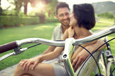 Couple in love sitting together on a bench with bikes in vacatio — Stock Photo