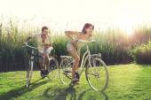 Couple having a bicycles race into the nature — Stockfoto