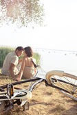 Couple with bicycle flirting in front of the lake — Stock Photo