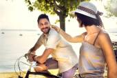 Couple having fun by bike on holiday to the lake — Stock Photo
