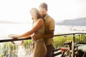 Couple in love joking  in a terrace on the lake — Stock Photo