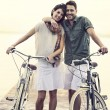 Couple in love pushing their bike toghether on a boardwalk — Stock Photo #62322145