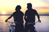 Silouette of couple carring bike on a boardwalk at sunset — Stock Photo