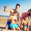 Haqppy young family on a tropical beach — Stock Photo #62387813
