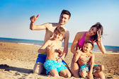 Haqppy young family on a tropical beach — Stockfoto