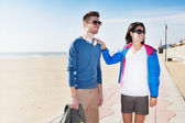 Young tourist couple standing on a beach boardwalk — Stock Photo