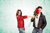 Happy Woman Putting Red Roses on Man Face — Stock Photo