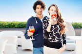 Young couple standing drinking cocktails — Stock Photo