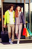 Young couple with luggage and shopping bags — Stock Photo
