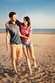 Smiling couple walking along the beach at sunset — Stock Photo