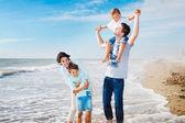 Family having fun on the beach to the sea — Stock Photo