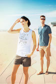Young tourist couple standing on a beach boardwalk — Foto Stock