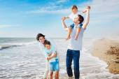 Family having fun on the beach to the sea — Stock Photo
