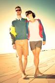 Romantic Young tourist couple standing on a beach at sunset — Stockfoto