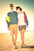 Romantic Young tourist couple standing on a beach at sunset — Stock Photo