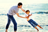 Father jokes affectionately with his son at sea — Foto Stock