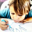 A young boy is doing drawing — Stock Photo #65078207