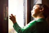 Concentrated child writes with his fingers on the foggy window — Stock Photo