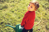 Small gardener carry heavy watering-pot — Stock Photo