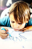 A young boy is doing drawing — Stock Photo