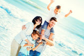 Family having walking on the beach to the sea — Stock Photo