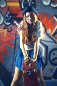 Girl with a skate with urban background — Stockfoto