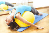 Woman making body exercises on a yellow ball — ストック写真