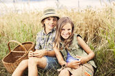 Friends picnicking together in a field of wheat — Stock Photo