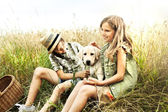Brother and sister in a wheat field with a dog — Stock Photo