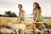 Children running with the dog in wheat at sunset — Stock Photo