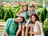 Parents play with children sitting on a bench at the greenhouse — Stock Photo