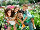 Happy family posing for a picture in a greenhouse — Stock Photo