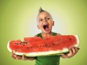 Punk boy eating a big slice of watermelon — Stock Photo